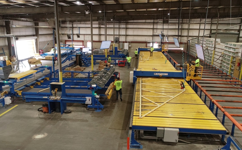 Automated Solutions Off-Site Construction - A wooden roof truss is being assembled using an automated process