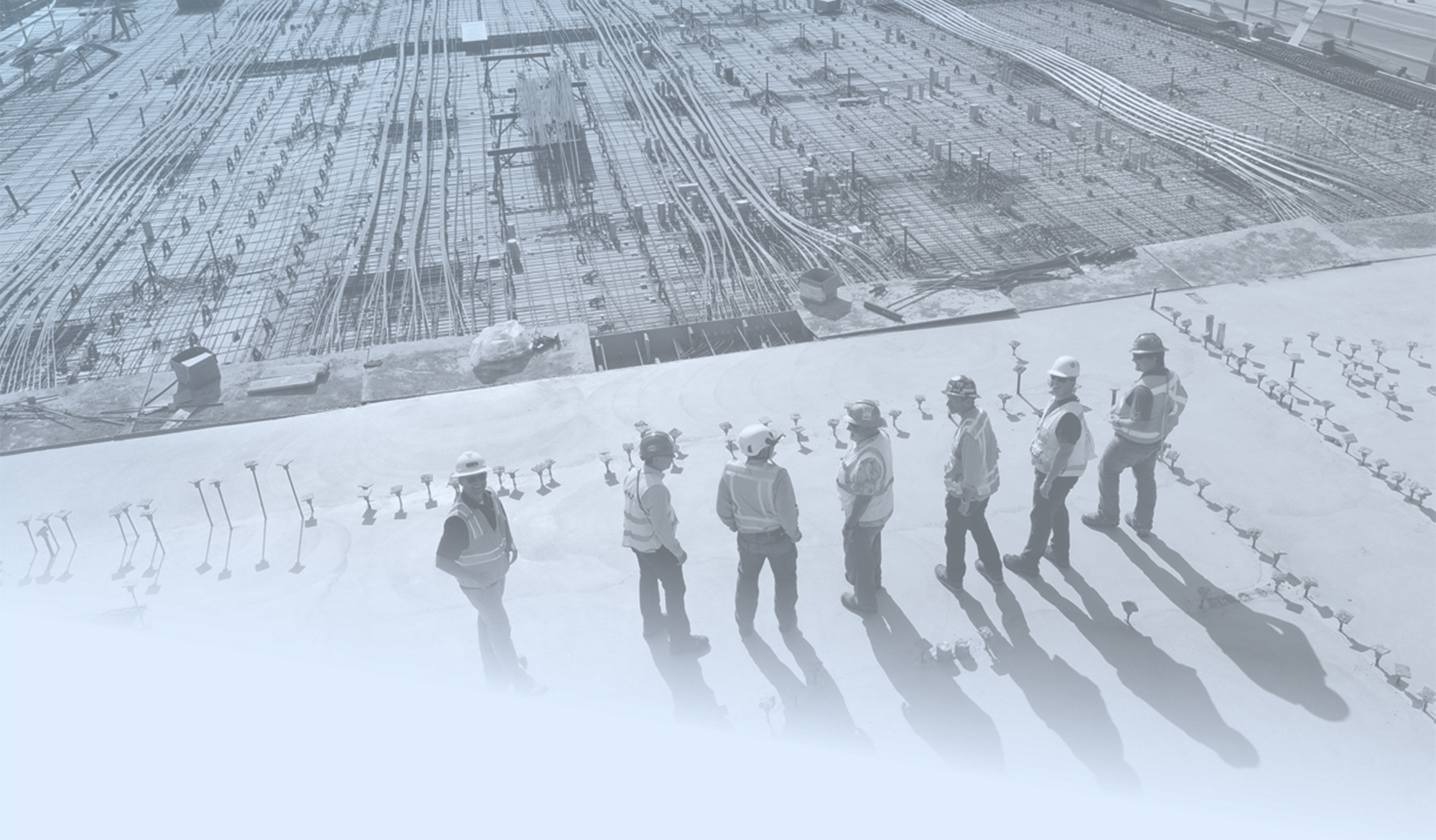 MiTek's History - A construction crew look over the foundation and MEP of a job site