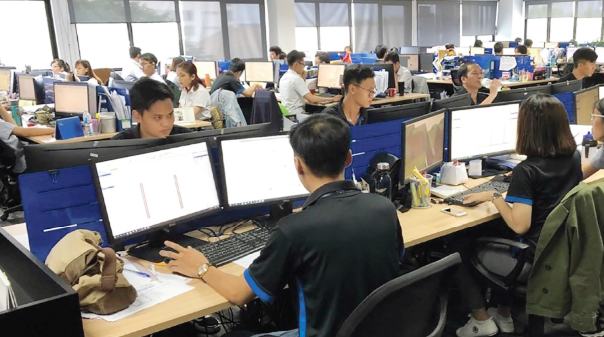 Solutions and Services Offered by MiTek - Engineering office with a number of employees working at their desks at MiTek