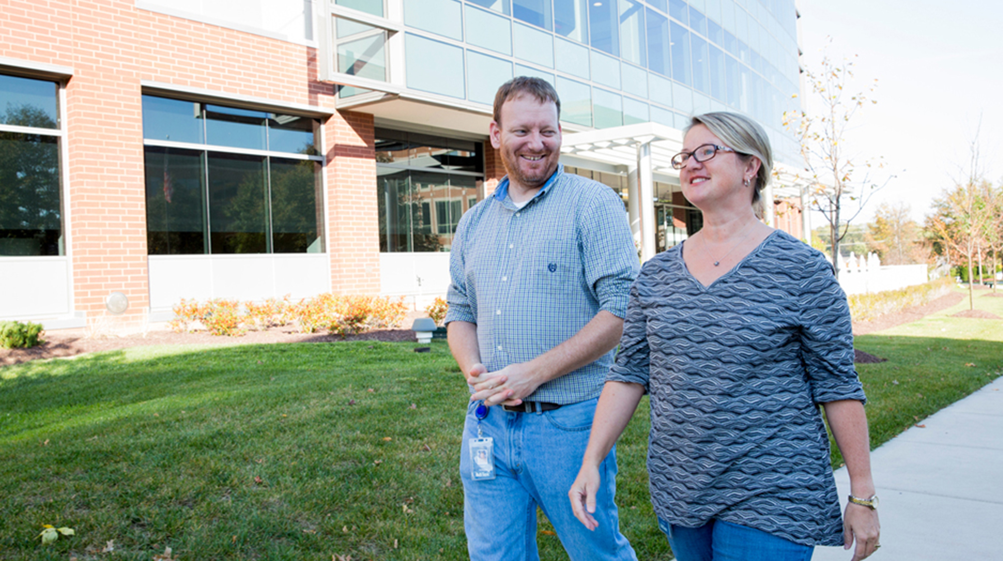 Career and Growth Opportunities at MiTek - A man and woman walk outside of the MiTek corporate office