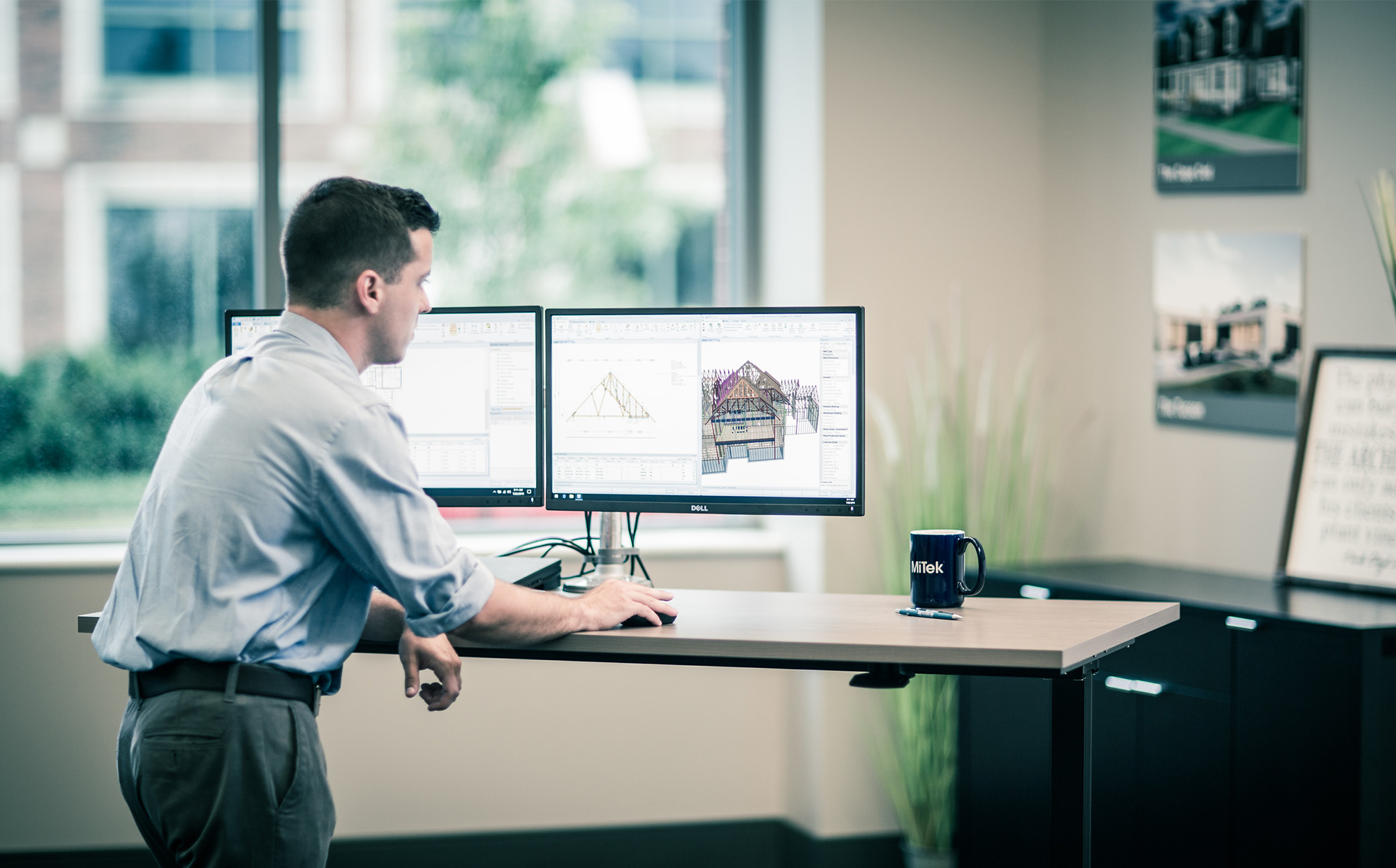 Solutions and Services Offered by MiTek - Man standing at desk working at a computer working on a 3D model of a house