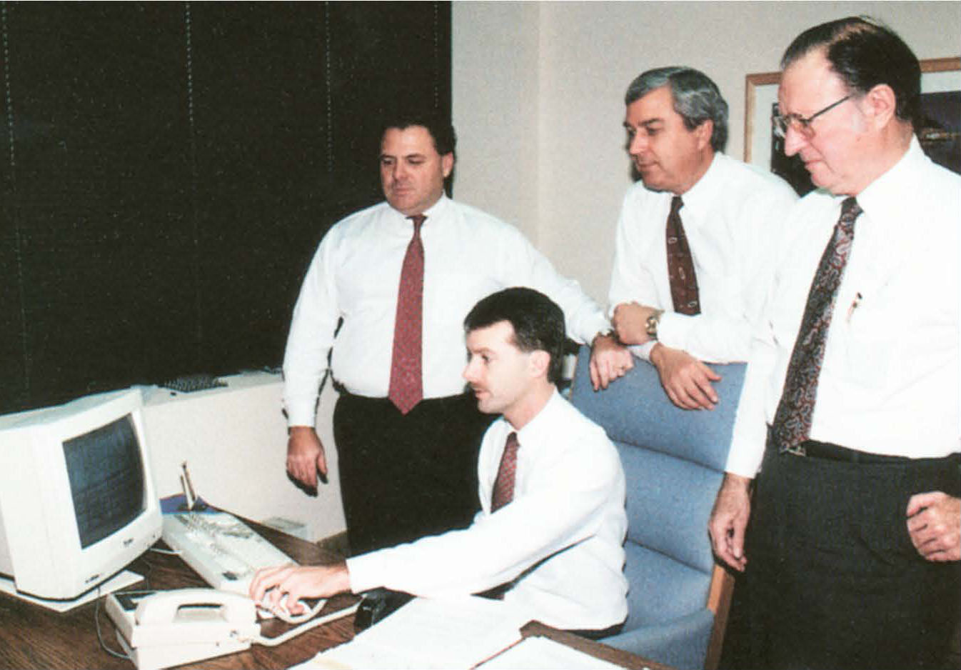 MiTek's History - Dave McQuinn and three men at a desk with late 1980s computer