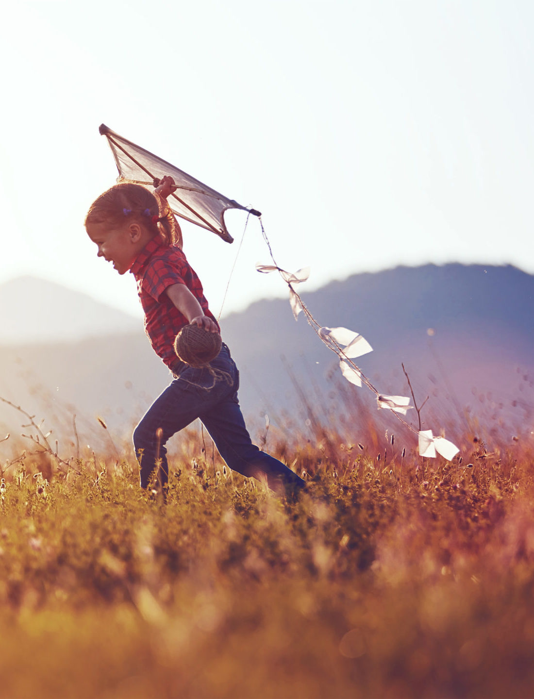 MiTek's commitment to communities - Girl running in the grass with a kite