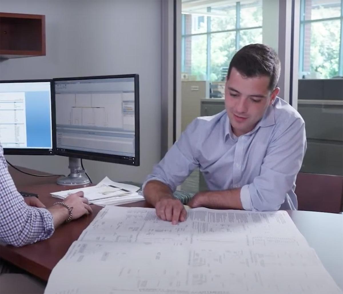 MiTek Detailing Services - Man sitting at desk looking at at detail drawings
