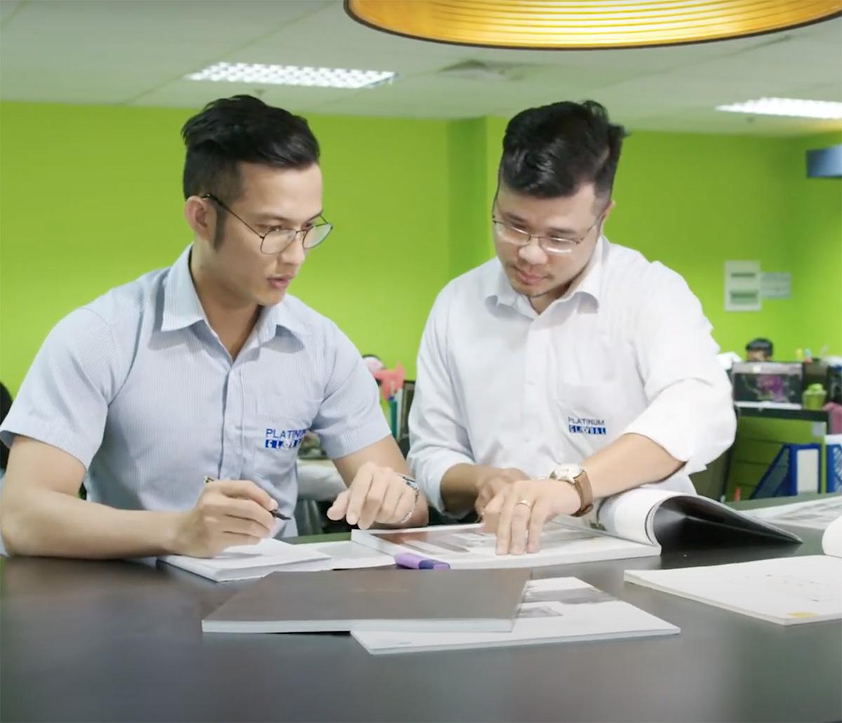 MiTek Execution Management Services - Two men at standing desk working on estimating