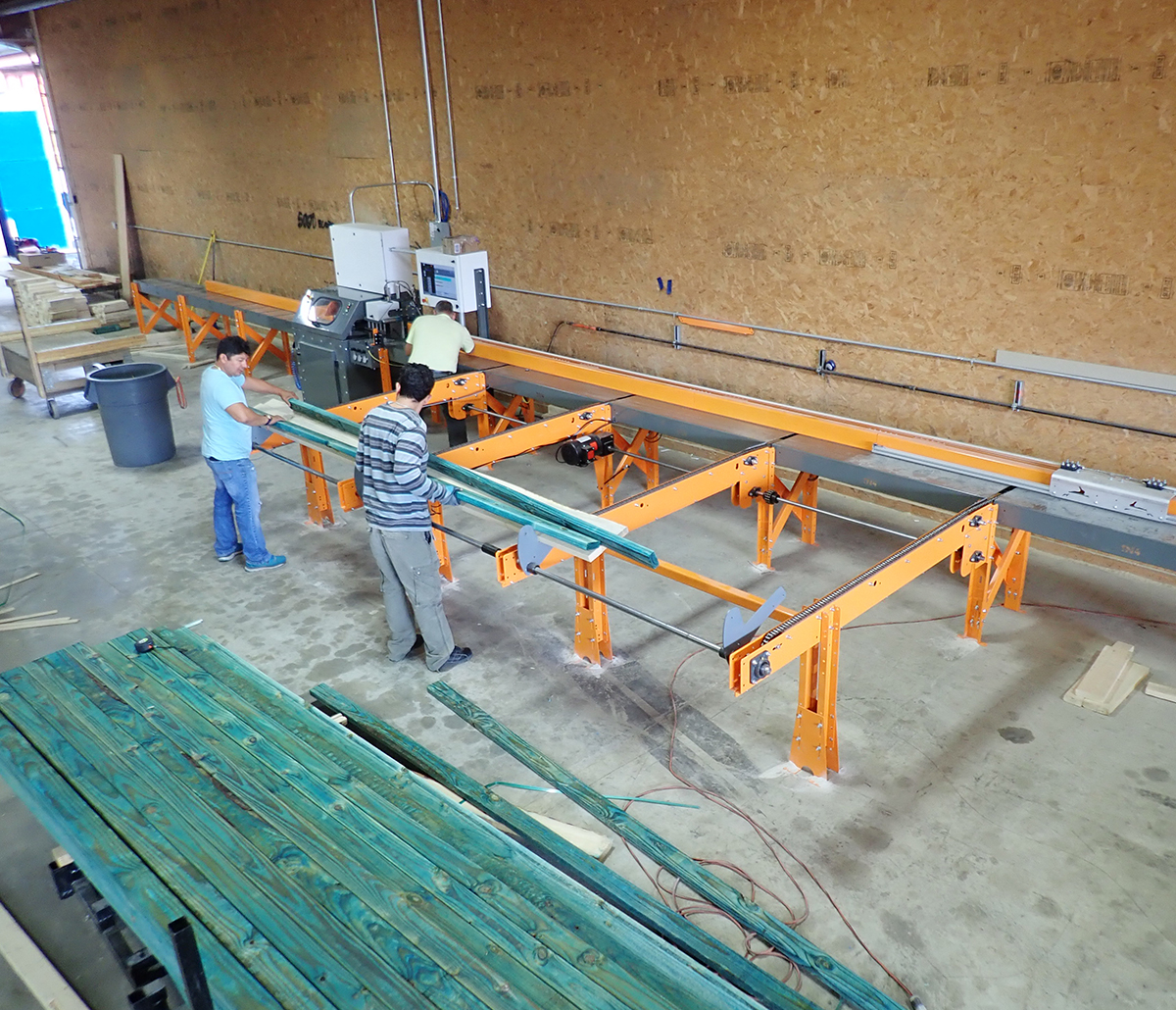 MiTek Hornet Saw Automated Solutions - Three men working with a Hornet Saw in a shop