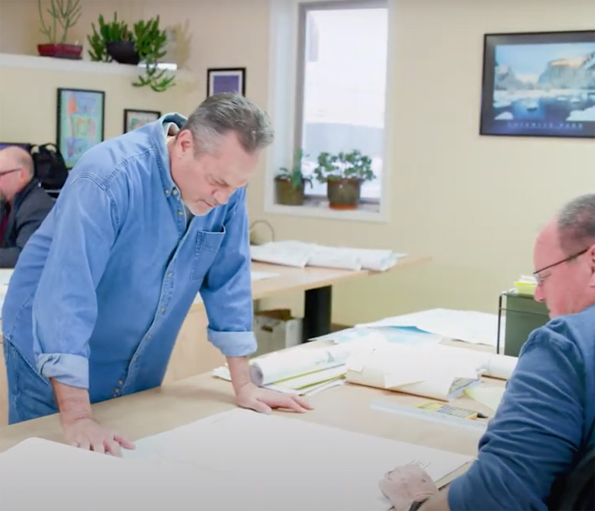 MiTek Resources Training Quality Control Management Services - Two men standing at desk looking over drawings