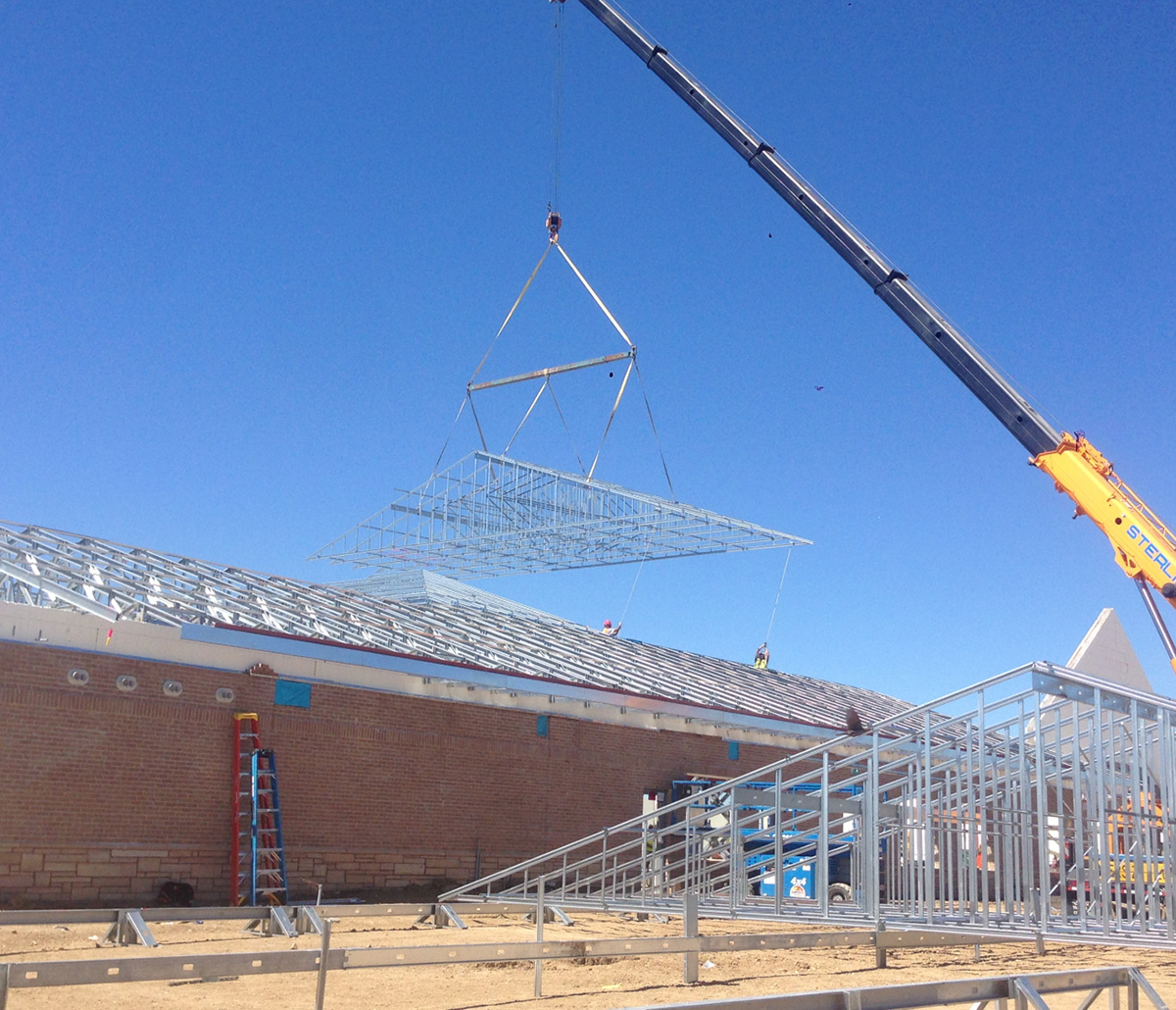 MiTek Ultra-Span Roof Truss Engineered Systems Products - Cold-formed steel roof truss being hoisted into place by crane