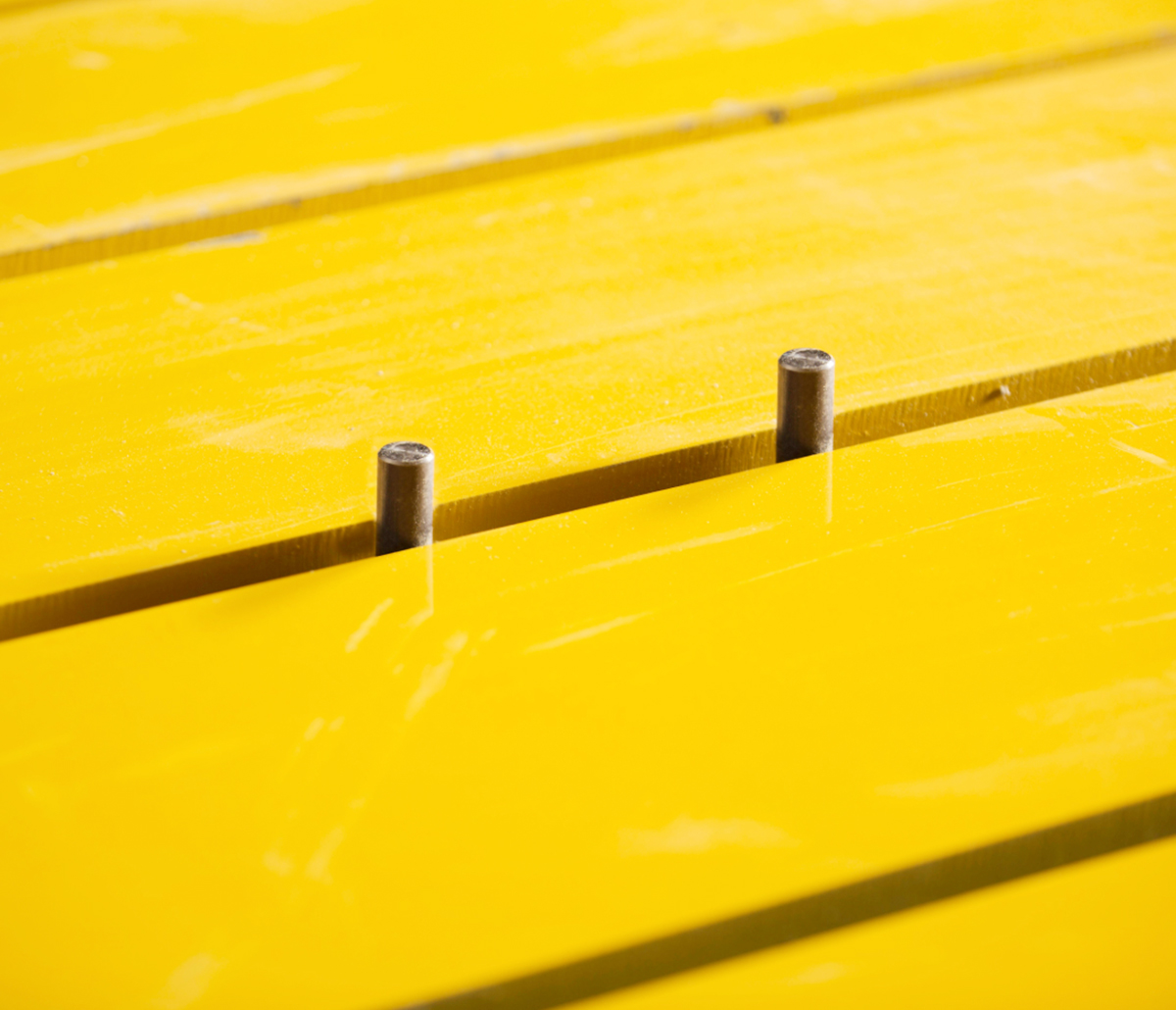 MiTek Wizard PDS Automated Solutions - Two metal pegs sticking up between two yellow boards